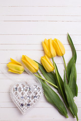 Yellow tulips flowers  and decorative heart on white painted wooden background. Selective focus. Place for text.