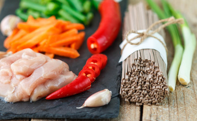 Ingredients for cooking buckwheat soba noodles with chicken and vegetables - dry raw buckwheat noodles , chicken, red pepper, green beans, carrots, garlic and green onions. Asian cuisine