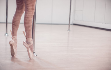 A ballet dancer standing in Pointe near pole in the empty studio with wooden floor. close-up.