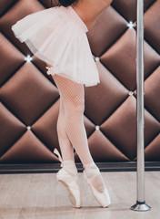 A ballet dancer standing in Pointe near pole. close-up.