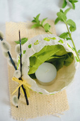 Easter decoration with a tee candle and a broken papier-mache eggshell with spring twigs