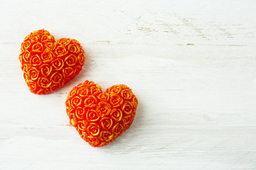 Two hearts of roses on a white wooden background