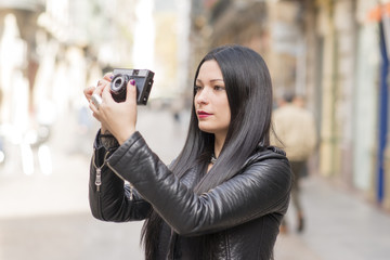 Hipster woman taking pictures with classica camera.