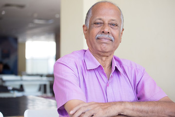Closeup headshot portrait of elderly gentleman arms crossed folded, in pink shirt smiling, content, isolated sitting indoors background