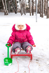 The child, a little girl sledding in the park in winter