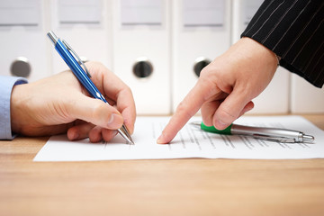 business woman is pointing where to sign on document, with docum