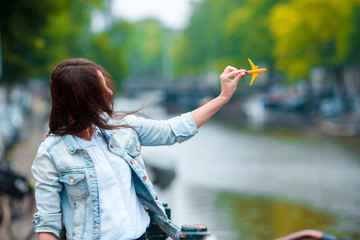Woman with airplane model background of canal in Amsterdam, Netherlands