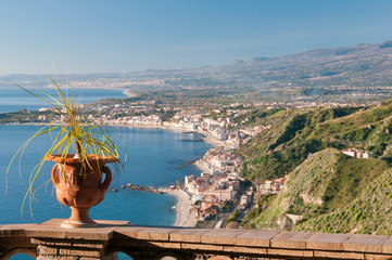 View of an ornamental vase in a panoramic balcony of the public garden in Taomina with the touristic village Giardini Naxos in the background