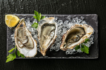 Zelfklevend Fotobehang Schaaldieren Oysters served on stone plate with ice drift