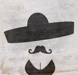 person wearing sombrero with mustache and cleavage on wood grain texture