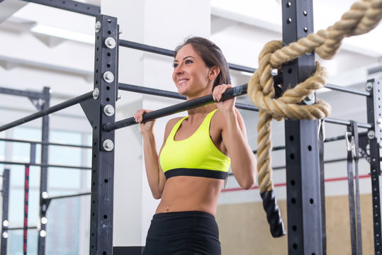 Fitness woman pull ups on horizontal bar in gym.
