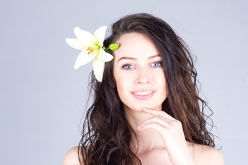 Woman with curly hair and lily in hair smiling with teeth and touching chin. Hawaiian mood.