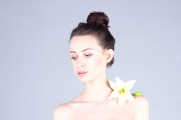 Attractive woman with flower on her shoulder looking down. Woman with clear skin. Skincare.