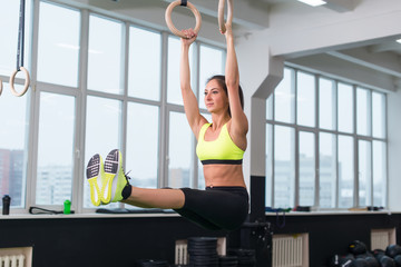Fit woman exercising with gymnastic rings raising legs in gym.