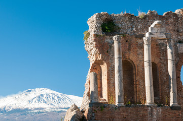 View of some columns in the stage of the greek theater in Taormina and a perspective of snowy mount Etna