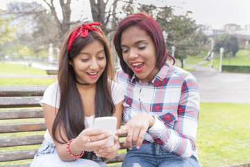 Two woman friends in surprise sharing social media in a smart phone.