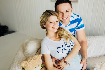 Portrait of expecting couple laughing happily at camera, embracing baby in belly together.