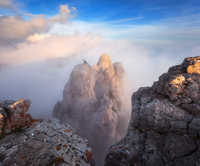 Wall Mural - Top of the mountains. High rocks with low clouds at sunset. Colorful nature background