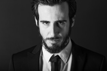 Bearded rude man looking at the camera on black background