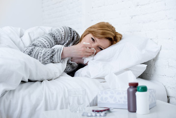 woman with sneezing nose blowing in tissue on bed suffering cold flu virus symptoms having medicines tablets pills