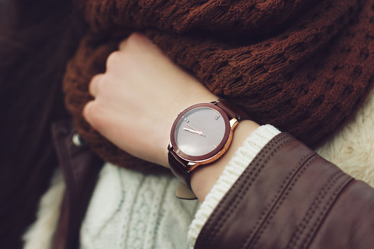 Elegant outfit. Closeup of brown wrist watch on the hand of stylish woman. Fashionable girl on the street. Female fashion. Toned