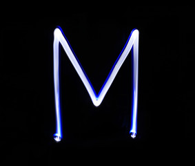 M Mike alphabet hand writing blue light  over black background.