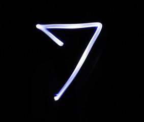 Seven blue light digit hand writing over black background.