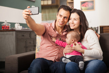 Pretty young family taking a selfie at home