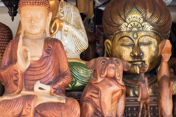 Wooden figures of Buddha, dogs, horses, and one of the metal