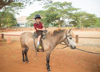 Little boy riding training horse