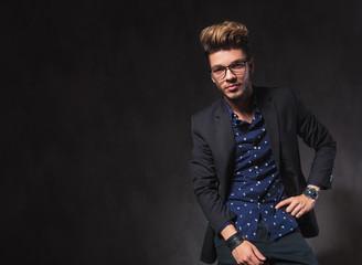 smart young man wearing glasses pose in dark studio