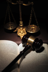 judge's gavel on a book near golden scale
