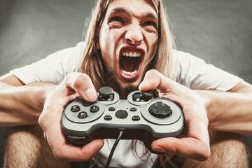 Stressed man playing on pad