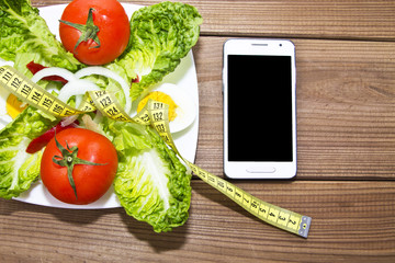 salad with mobile phone on wooden background
