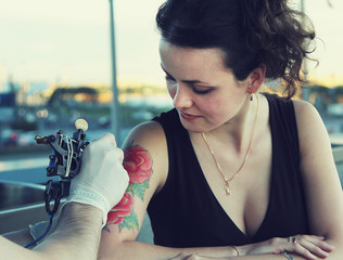 tattooer showing process of making a tattoo on young beautiful smiling hipster woman with red curly hair. Tattoo design in the form of rose. Vintage picture