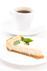 Wedge of baked cheesecake with sprig of mint