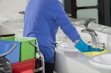 rubber gloved hand cleaning sink with duster