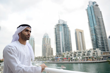Young Emirati man standing by the canal in Dubai Marina, UAE