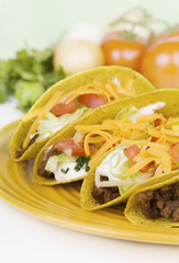 Four Tacos on a Plate – Vertical format of four ground beef tacos on a plate. Fresh ingredients in the background.