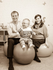 Photo in retro style of young family jumping on fitness balls