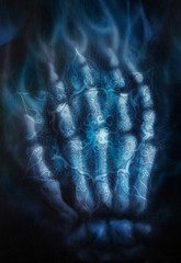 Painting skeleton hand, on black background and ornamental mandala. Airbrush painting.