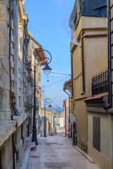 Narrow street between buildings in city. Picture of narrow isola