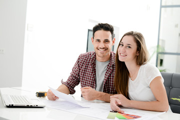 young couple planning decoration project of their new home with blueprint