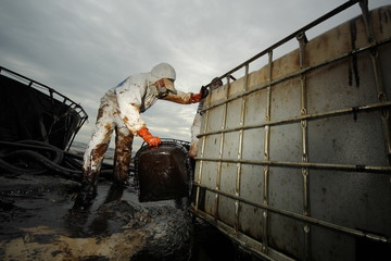 Worker and Tanks contain crude oil that draw from oil spilled accident on Ao Prao Beach at Samed Island on July 31,2013 in Rayong,Thailand