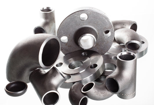 Steel welding fittings on group. Flanges, elbow, tees and plug on white space.