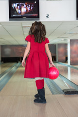 Rear view of a girl holding a bowling ball at bowling alley