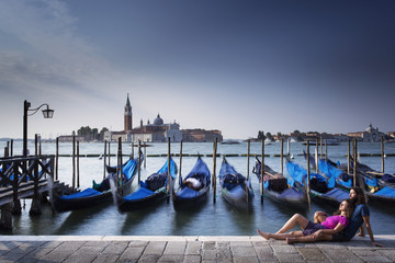 Couple relaxing in venice with blue boats in background