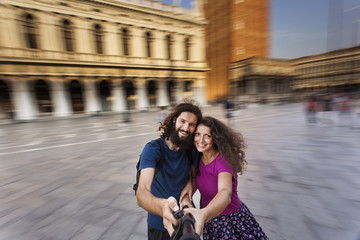 Cheerful tourists making selfie photo in Venice