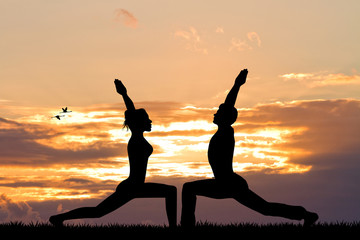 couple doing yoga at sunset