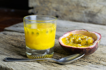 Passion fruits with glass of passion fruit juices on wooden